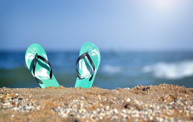 Zapatillas en la arena al mar. vacaciones. sandalias