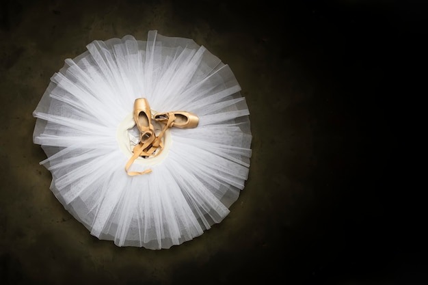 Zapatillas de ballet con cintas sobre un tutú blanco en un estudio de danza