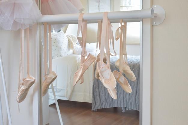 Zapatillas de ballet cuelgan en barra en dormitorio