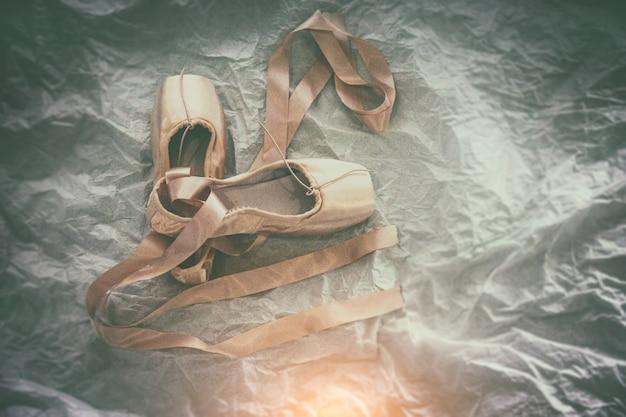 Zapatillas de ballet rosa sobre fondo, estilo clásico de película antigua, luz borrosa alrededor