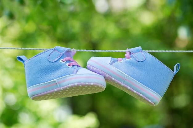 Zapatillas de bebé colgadas en el tendedero sobre fondo verde