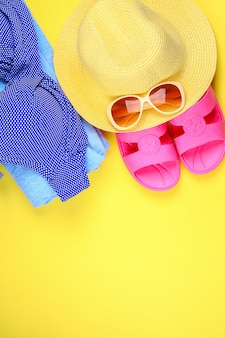 Zapatillas, bikini traje de baño, toalla, sombrero y gafas de sol sobre un fondo amarillo pastel.