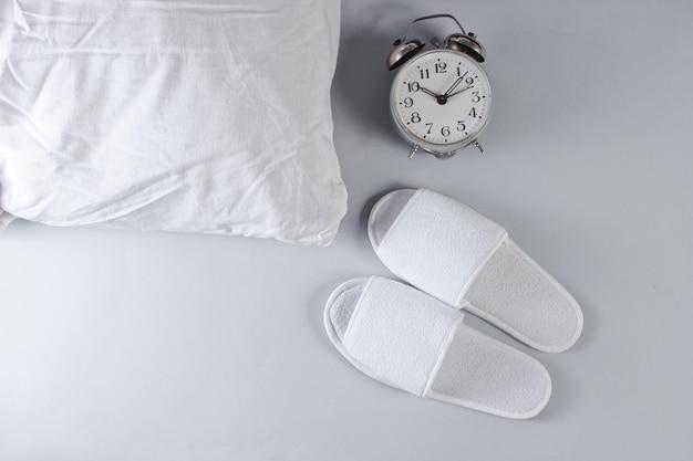 Zapatillas blancas para dormir, despertador y almohada sobre superficie gris.