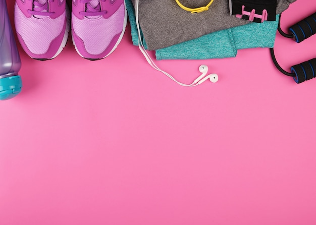 Zapatillas de color rosa para mujer, una botella de agua, guantes y una cuerda para saltar para hacer deporte.