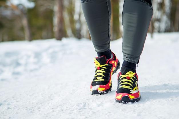 Zapatillas para correr: primer plano del corredor de fitness deportivo femenino que se prepara para correr al aire libre en invierno