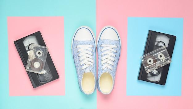 Zapatillas de deporte, cintas de audio, cintas de video en una superficie rosa pastel azul. atributos retro de los años 80. vista superior