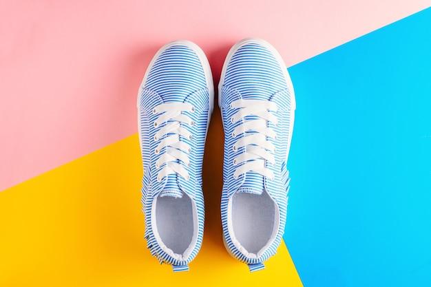 Zapatillas de deporte femeninas rayadas azules en una opinión superior del fondo colorido. fondo plano laico minimalista.