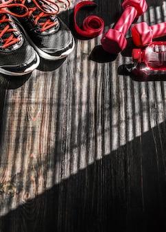 Zapatillas de deporte con mancuernas y una botella de agua. vista plana todo en un color.