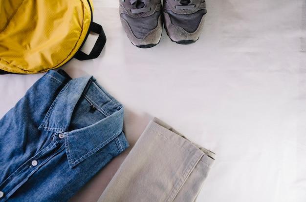 Zapatillas de deporte y mochila cerca de la camisa y los pantalones