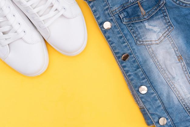 Zapatillas de deporte y vaqueros blancos femeninos en fondo amarillo con el espacio de la copia.