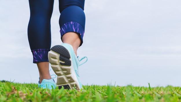 Zapatillas deportivas del atleta de la mujer de la aptitud mientras que camina en el parque al aire libre.