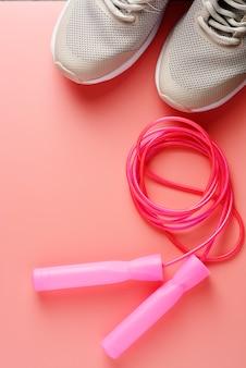 Zapatillas deportivas y cuerda de saltar sobre fondo rosa.