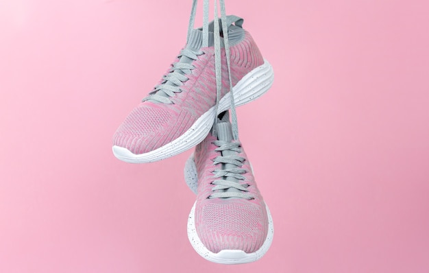 Zapatillas deportivas femeninas para correr o fitness colgando sobre fondo rosa