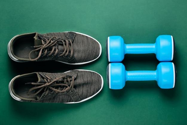 Zapatillas deportivas y pesas en la mesa verde.