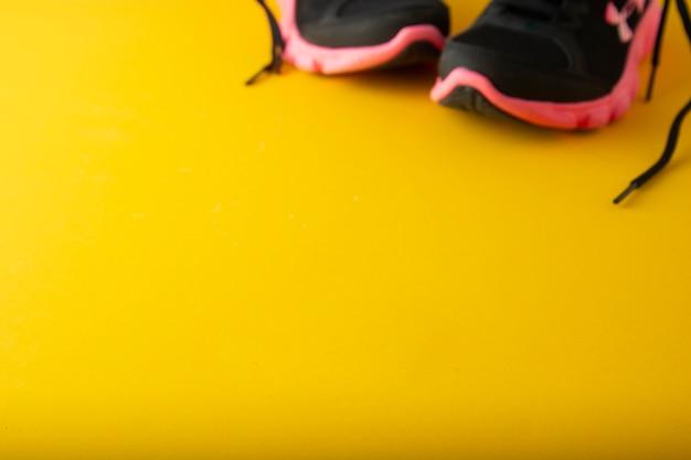 Zapatillas deportivas, ropa deportiva, sobre fondo amarillo con copia espacio.