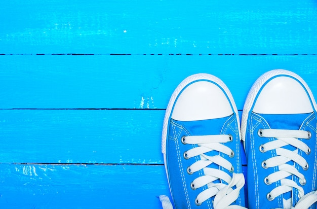 Zapatillas deportivas de textil azul con cordones blancos.