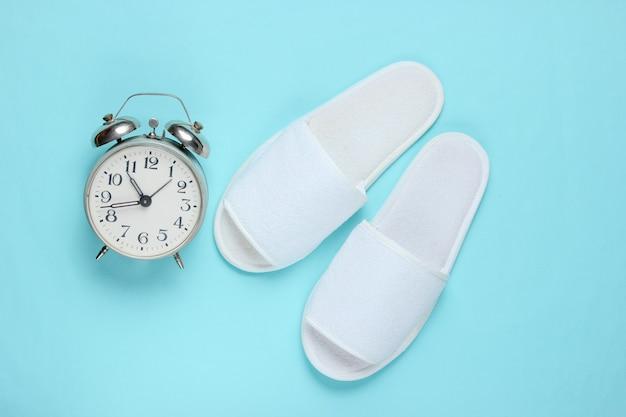 Zapatillas de hotel blanco y despertador sobre superficie azul.