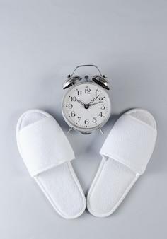 Zapatillas de hotel blanco y despertador sobre superficie gris. hora de dormir.