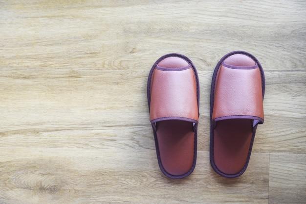 Zapatillas marrones en el piso de madera