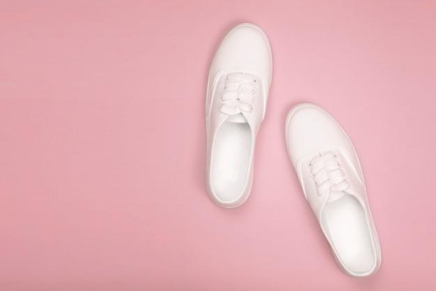 Zapatillas de mujer blancas sobre un fondo rosa. lay flat, vista superior y espacio de copia en estilo minimalista. concepto de blog de moda, enfoque suave