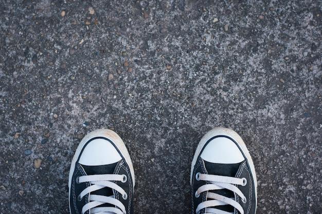 Zapatillas negras con hombre inconformista sobre hormigón.