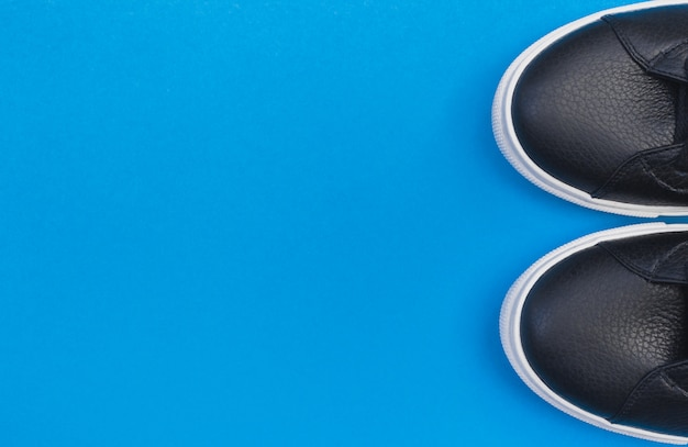 Zapatillas negras sobre fondo azul. endecha plana, vista superior fondo mínimo.