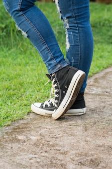 Zapatillas negras de zapatillas en carretera de hormigón.
