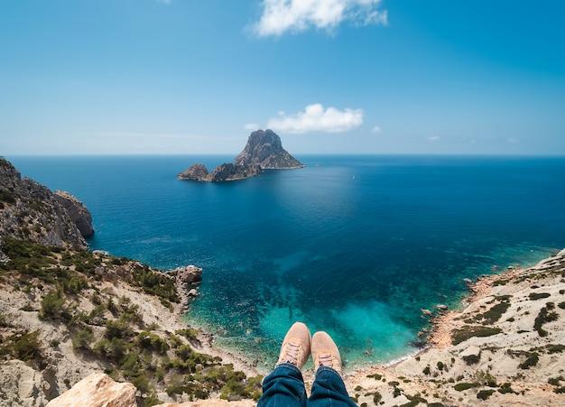 Zapatillas y piernas de una mujer, colgando del acantilado del parque natural de cala d'hort, en ibiza, españa. al fondo, el mar turquesa del mediterráneo y los islotes de es vedrá y es vedranell.