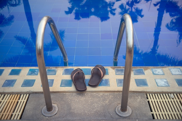 Zapatillas en la piscina de entrada