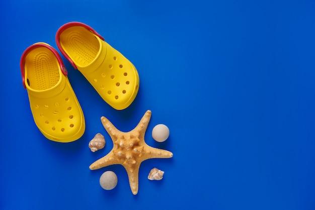 Zapatillas de playa con estrellas de mar y conchas marinas en azul. endecha plana. vista superior.