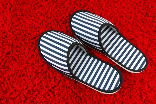 Zapatillas de rayas en la superficie de la alfombra