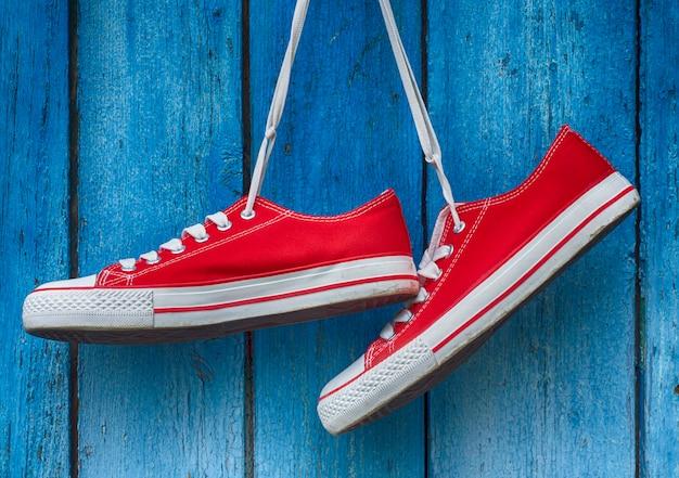 Zapatillas rojas colgadas en un azul de madera.