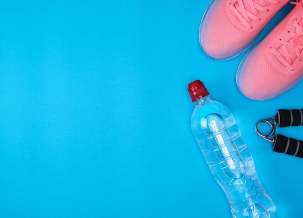 Zapatillas rosas, botella de agua de plástico y expansor deportivo.