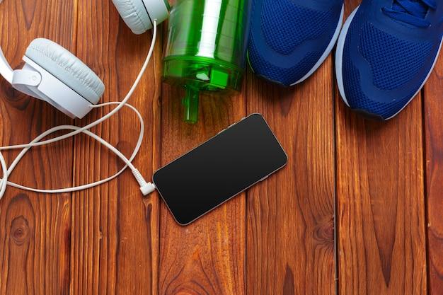 Zapatillas y teléfono móvil con auriculares en mesa de madera.