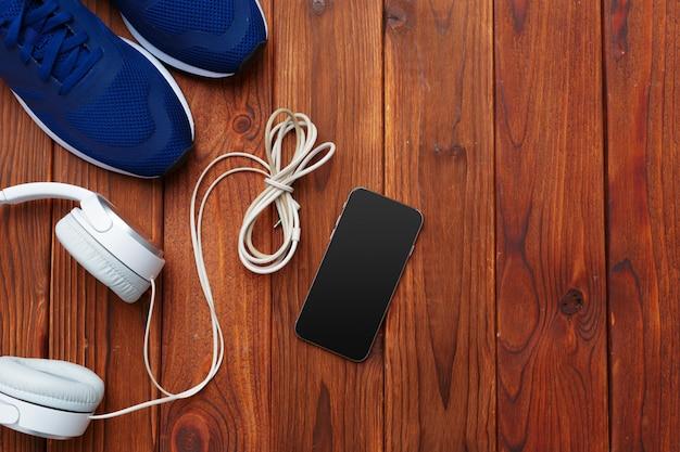 Zapatillas y teléfono móvil con auriculares en mesa de madera