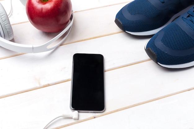Zapatillas y teléfono móvil con auriculares.