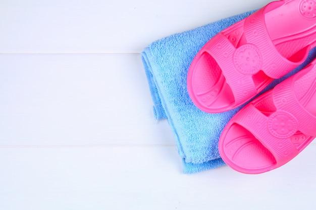 Zapatillas, toalla sobre suelo de madera blanca.