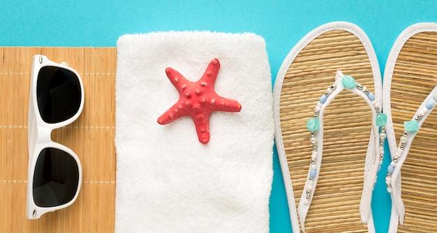 Zapatillas de verano con toalla y gafas de sol.