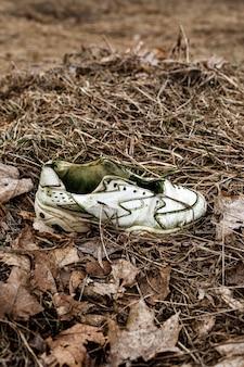 Zapatillas viejas rotas en la hierba sucia.