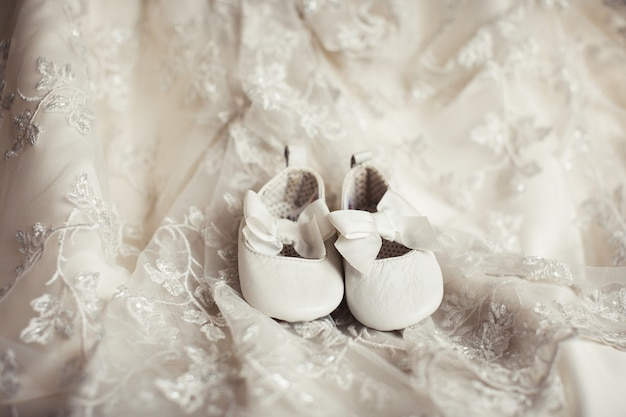 Zapatitos de bebé sobre tela de encaje