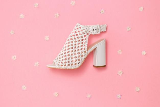 Zapato de cuero de moda sobre fondo rosa con flores. calzado de verano para mujer. endecha plana. la vista desde arriba.