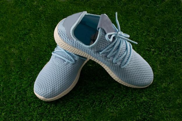 Zapato deportivo azul sobre el cristal verde