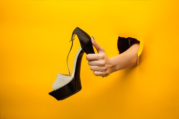 Zapato de mujer marrón en mano aislado
