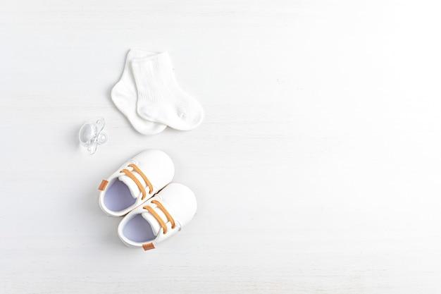 Zapatos y accesorios de bebé neutros en cuanto al género. moda recién nacida orgánica, marca, idea de pequeña empresa. baby shower, invitación de bautismo, tarjeta de felicitación. endecha plana, vista superior