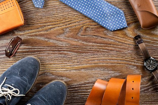 Los zapatos y los accesorios de los hombres yacían planos sobre una tabla de madera. copia espacio