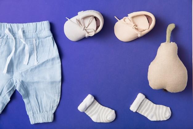 Zapatos de bebé de color rosa; calcetín y pantalón de bebé con pera rellena sobre fondo azul brillante