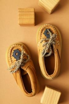Zapatos de bebé y cubos de madera sobre fondo beige.