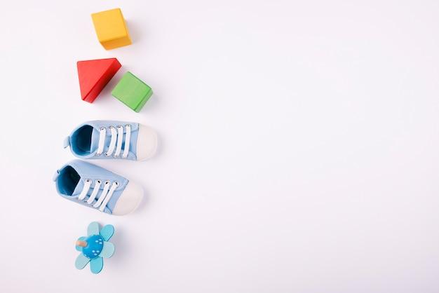 Zapatos de bebé y juguetes copia espacio
