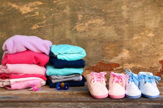 Zapatos de bebé, ropa y chupetes rosa y azul sobre el fondo de madera vieja.