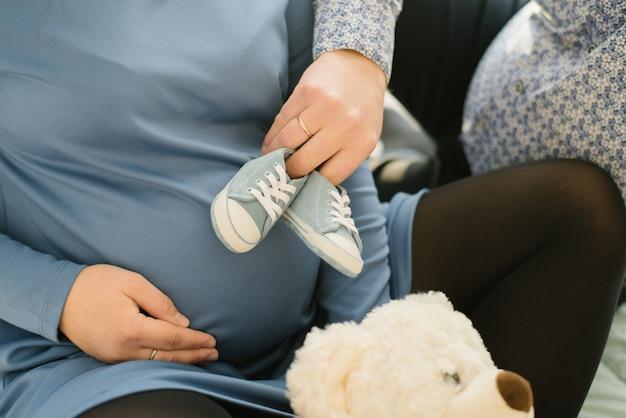 Zapatos de bebé, zapatillas de mezclilla para el bebé en manos del futuro papa, que puso los zapatos en el vientre de la esposa embarazada.